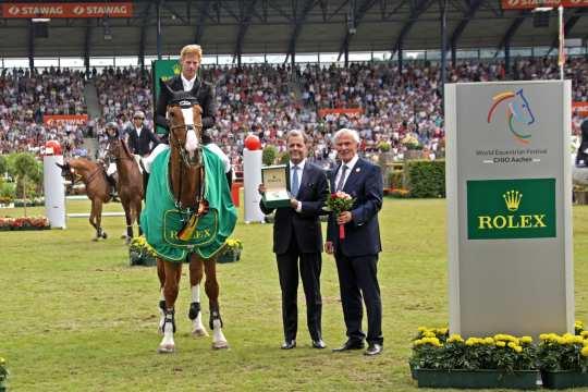 Dem Sieger Marcus Ehning gratulieren Rafael Rolli, Geschäftsführer Rolex Deutschland GmbH, und ALRV-Präsident Carl Meulenbergh. Foto: CHIO Aachen/ Michael Strauch