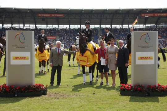 The winner is congratulated by Katja Busch, Chief Commercial Officer DHL and Carl Meulenbergh, President of the Aachen-Laurensberger Rennverein e.V. (right) and Breido Graf zu Rantzau, President of the National Federation.