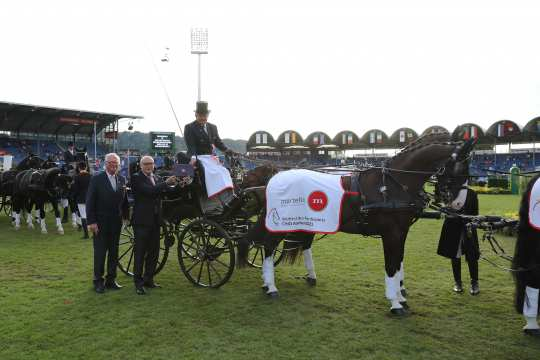 """ALRV Vice President Baron Wolf von Buchholtz and Wolfgang """"Tim"""" Hammer, Managing Director Martello Immobilienmanagement GmbH & Co. KG, congratulate four-in-hand driver Boyd Exell on his victory. Photo: CHIO Aachen / Michael Strauch"""