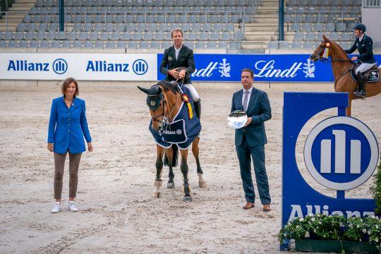 The winner is congratulated by Oliver Leber, Allianz Köln, and Stefanie Peters, President of the Aachen-Laurensberger Rennvereins e.V.. Picture: Aachen International Jumping/ Arnd Bronkhorst.