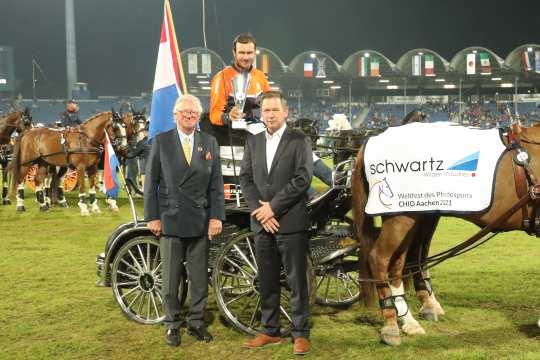 Benjamin Wilden, sales manager and member of the management of schwartz GmbH and ALRV Vice President Baron Wolf von Buchholtz (left) congratulate the winner. (Photo: CHIO Aachen / Michael Strauch).