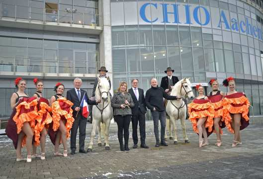 """It shows f.t.l. Carl Meulenbergh, Dr. Angelika Ivens, Frank Kempermann and Uwe Brandt, framed by Angela Egert and Uli Höfert from the """"Liberté Stud"""" in Königswinter with their Camargue horses and cancan dancers from the Dance Company TNBOOM of Marga Render. Photo: CHIO Aachen/Holger Schupp"""