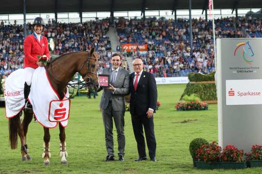 "Beezie Madden is congratulated by Norbert Laufs, CEO Sparkasse Aachen, and supervisory member Wolfgang ""Tim"" Hammer."