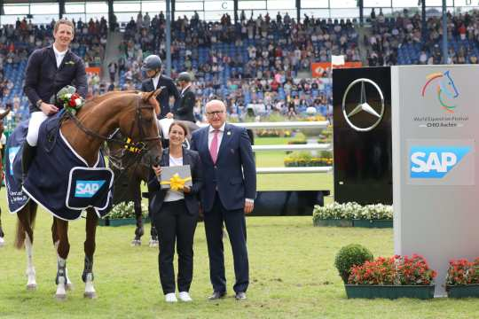 "The winner is congratulated by Aileen Trunk, SAP equestrian sponsoring, and Wolfgang ""Tim"" Hammer, member of the ALRV supervisory board."