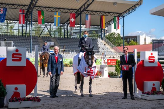 The winner Chris Pratt is congratulated by Wilfried Nellessen, Member of the Board of Sparkasse Aachen (right) and ALRV Supervisory Board Member Baron Wolf von Buchholtz. Photo: Aachen International Jumping/ Arnd Bronkhorst