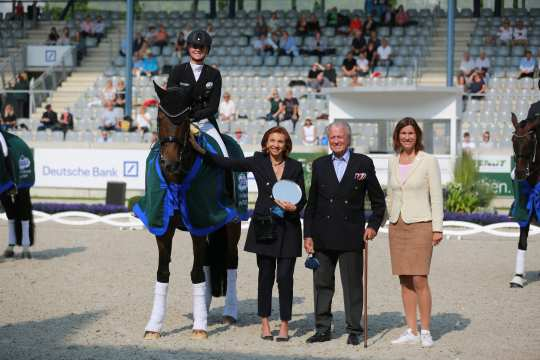 From left: Ms. Marina Meggle, deputy Chairwoman of the Management Board of the Toni Meggle Foundation, Mr. Toni Meggle, Chairman of the Management Board of the Toni Meggle Foundation, and ALRV President Stefanie Peters congratulate the winner in the Deutsche Bank Stadium. Photo: CHIO Aachen / Michael Strauch